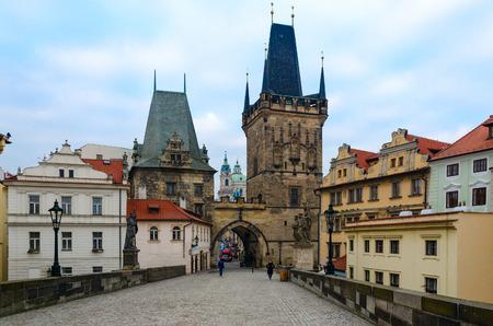 PRAGUE, CZECH REPUBLIC - JANUARY 22, 2019: Unidentified tourists are on Charles Bridge. Mala Strana Bridge Tower, Prague, Czech Republic