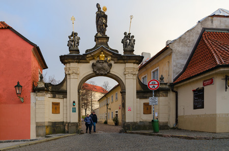 PRAGUE, CZECH REPUBLIC - JANUARY 22, 2019: Baroque gate with sculpture of St. Norbert, founder of Premonstrant Order, Strahov Monastery. Unknown people leave monastery Editorial