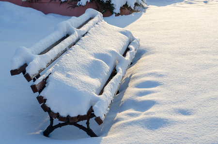 Snow-covered bench on city street after heavy snowfall