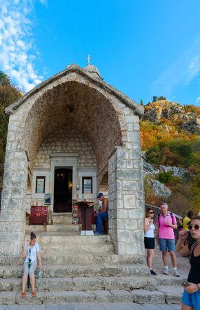 KOTOR, MONTENEGRO - SEPTEMBER 8, 2017: Unknown tourists are located near chapel of Salvation of Virgin (Church of Virgin Health) in Kotor, Montenegro 新聞圖片