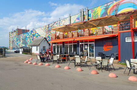 MINSK, BELARUS - AUGUST 12, 2019: Unidentified people relax in outdoor cafe on Oktyabrskaya street, Minsk, Belarus. Graffiti on wall of industrial building, created as part of Vulica Brasil festival 스톡 콘텐츠 - 133365533