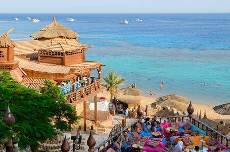 Sharm El Sheikh, Egipt - 19 września 2019: Niezidentyfikowani ludzie odpoczywają w popularnej kawiarni Farsha z oryginalnym wnętrzem na brzegu Morza Czerwonego w dzielnicy Hadaba, Sharm El Sheikh, Egipt