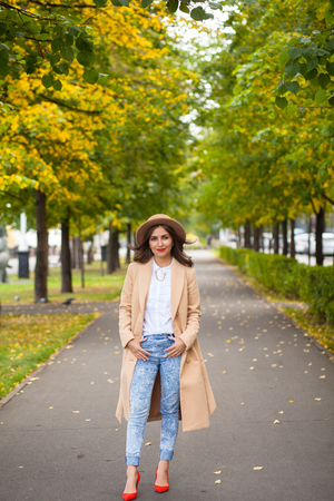 She walks down the avenue in a coat, hat, red shoes on the background of autumn trees