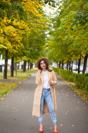 lighthearted: She walks down the avenue in a coat, hat, red shoes on the background of autumn trees