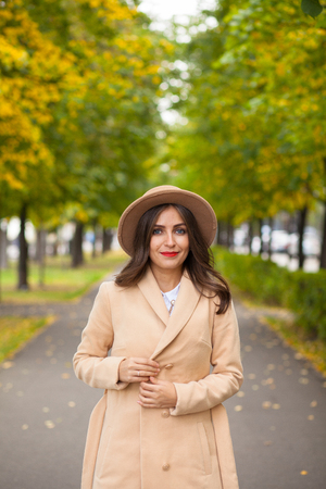 Portrait of a girl walking along the alley in a coat, a hat on a background of autumn trees Stock Photo