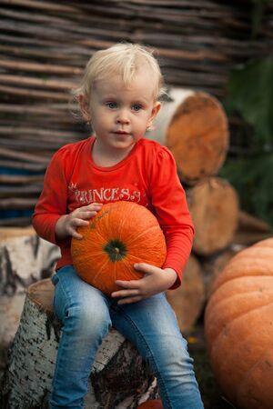A girl holds a pumpkin .berezy. rural landscape