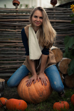 girl sits on a birch stump with the pumpkins. against the backdrop of sunflowers Stock Photo