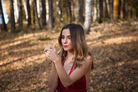 beautiful girl in a red dress doing make-up in the forest Stock Photo