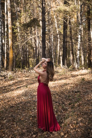 beautiful girl in a red dress in the autumn forest
