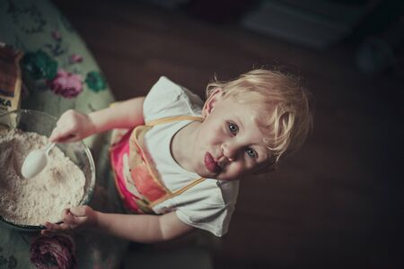 stirred: little girl baking cookies. Flour stirred in a cup Stock Photo
