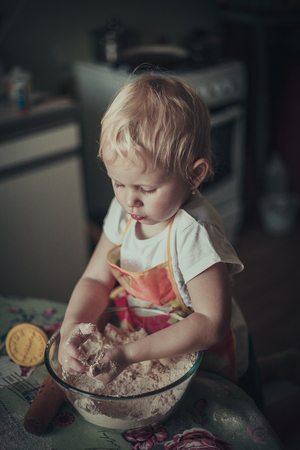 stirred: little girl baking cookies. Flour stirred in a cup of her hands