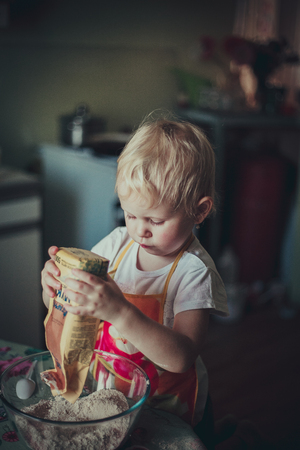 home cooking: little girl baking cookies. Pour the flour into the cup Stock Photo