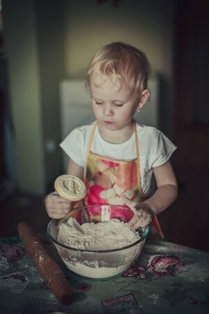christmas baker's: little girl baking cookies. Hands in flour