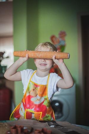 little girl baking cookies, rolls the dough