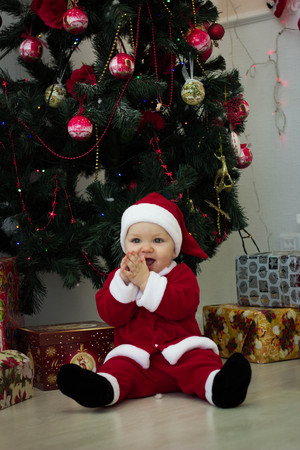 baby sitting in a suit of santa claus at the christmas tree with gifts stock photo