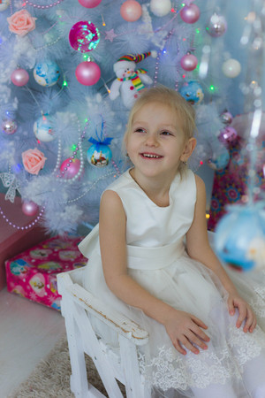 little girl near a white Christmas tree Stock Photo