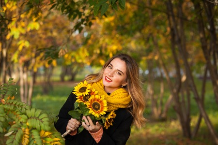 Beautiful girl with sunflowers in the autumn rowan