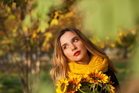 persimmon: Beautiful girl with sunflowers in the autumn rowan