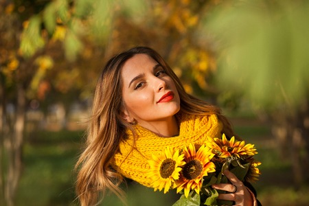 Beautiful girl with sunflowers in the autumn rowan