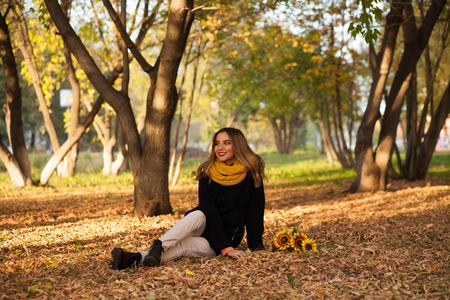 Beautiful girl with sunflowers sitting in autumn leaves