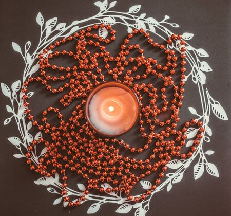 glimmered: Red Christmas candle and Christmas beads on a black background with a wreath Stock Photo