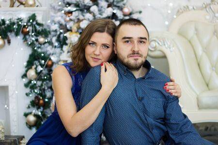 marchers: husband and wife in a New Years tree hall with fireplace Stock Photo
