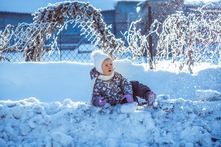 child playing in the snow drifts of snow