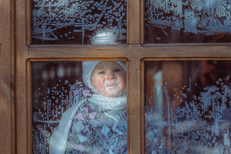 chilly: child for icy window on a cold winter day Stock Photo