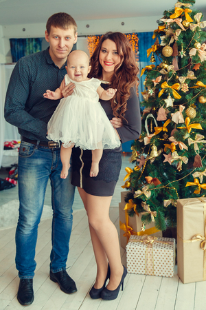 baby near christmas tree: a young family with a baby near Christmas tree with presents. Stock Photo