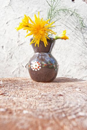 stillife: Dark crock with yellow wildflowers. Grunge stillife