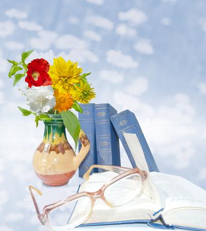 Vase avec des fleurs colorées, des livres bleus, des livres ouverts et des verres. Fermer. Carte postale bleue lumineuse. Le jour du professeur Banque d'images