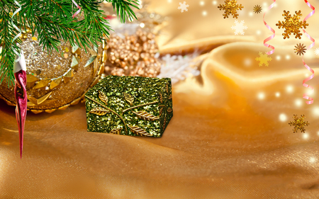 satin background: Christmas gift box, branch of green fir on the gold satin background