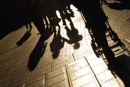 strangers: Shadows of people walking on the city street Stock Photo