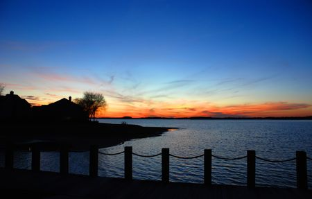 sunset lake: Lake house silhouette during the sunset with deep blue dramatic sky colors. Norman Lake, Northern Carolina, USA. Stock Photo