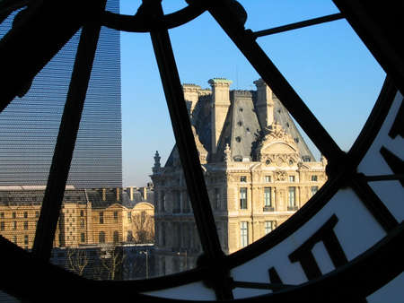 Tower of Louvre palace through the Orsay museum clock in Paris, France photo