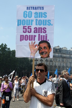 overhaul: PARIS - JUNE 24: A man holding the poster 60 years for all and 55 for him during Frances nationwide strike against pension overhaul where bill raising the retirement age from 60 to 62 is to be voted in September on June 24, 2010 in Paris, France