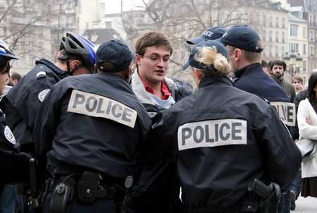 fervent: PARIS - MARCH 22: Fervent Catholic gets arrested for causing steer and throwing eggs and water at the ACT UP protesters by Notre-Dame Cathedral on March 22, 2009 in Paris, France.