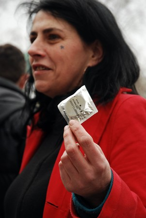 give out: PARIS - MARCH 22: Members of the Act Up organisation give out condoms by Notre-Dame Cathedral to protest against Pope Benedict XVIs remarks on condoms and abortion on March 22, 2009 in Paris, France.