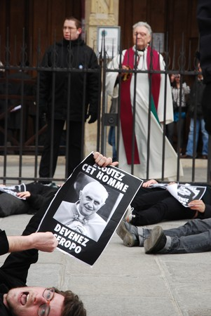 PARIS - MARCH 22: Members of the Act Up organisation lay down in front of Notre-Dame Cathedral to protest against Pope Benedict XVIs remarks on condoms and abortion with the Catholic priest watching on March 22, 2009 in Paris, France. The poster reads L