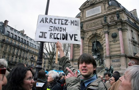 prohibits: PARIS - APRIL 8: A man protests the law, which prohibits to provide aid to illegal immigrants on April 8, 2009 at Place St. Michel in Paris, France. The poster says Arrest me, otherwise I do it again Editorial