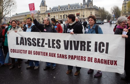 prohibits: PARIS - APRIL 8: People gathered to protest the law, which prohibits to provide aid to illegal immigrants in France on April 8, 2009 at Place St. Michel in Paris, France. The banner says Let them live here