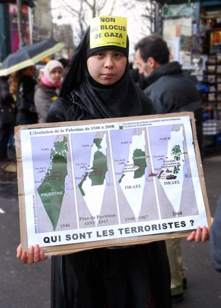 manifestation: PARIS - MARCH 28: Anti-Israeli proteser holds a poster during the manifestation on March 28, 2009 at Place du Chatelet, Paris, France. The poster says Who are the terrorists?