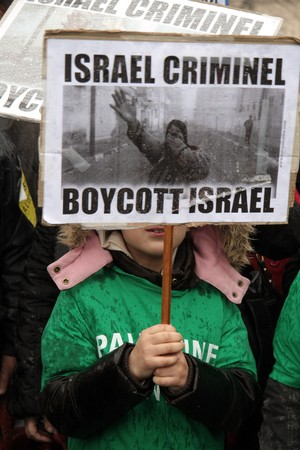 boycott: PARIS - MARCH 28: A child holds a poster during the Anti-Israeli manifestation on March 28, 2009 at Place du Chatelet, Paris, France. The poster says Israel is criminal. Boycott Israel