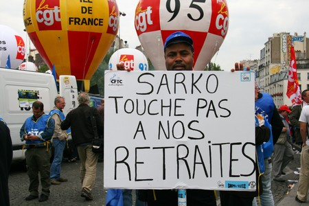 syndicate: PARIS - SEPTEMBER 23: A man holds the poster Sarkozy dont touch our retirement during Frances nationwide strike against the raise of the retirement age from 60 to 62 on September 23, 2010 in Paris, France