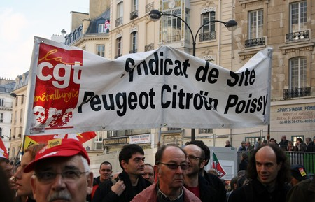 syndicate: PARIS - OCTOBER 28: Trade Union of the Peugeot Citroen concern employees march during the strike against the retirement age reform on October 28, 2010 in Paris, France