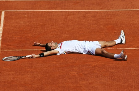 lies down: PARIS - MAY 21: Novak Djokovic of Serbia lies down at the centre court during the exhibition match  at French Open, Roland Garros on May 21, 2011 in Paris, France. Editorial