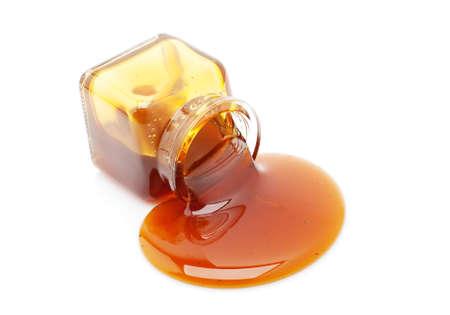 jarabe: La miel derrame de un frasco de vidrio aislado en blanco Foto de archivo