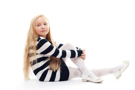 little girl sitting on the floor. Isolated on white. photo