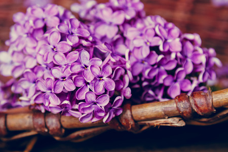 material flower: lilac bouquet on a table in a rural basket