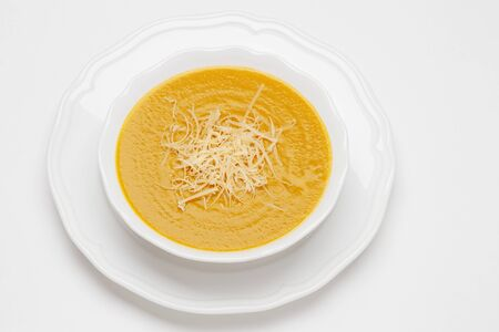 Plate of pea cream soup served with cheese on white background